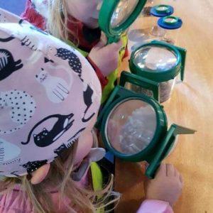 nyfikna barn undersöker med förstoringsglas